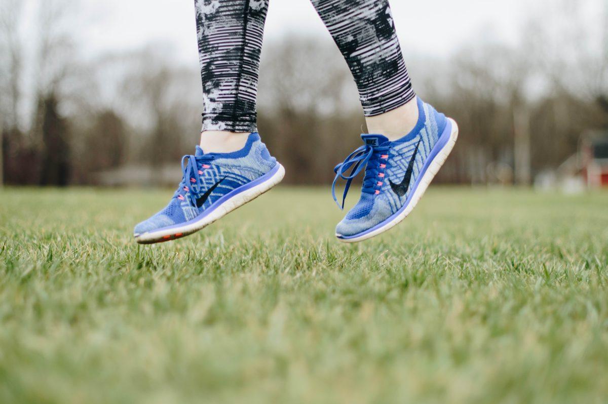 kobieta na zielonej łące w butach sportowych skacze i czuje się lekko